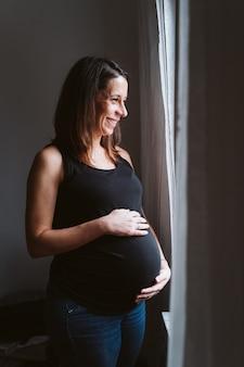 Jonge zwangere vrouw thuis