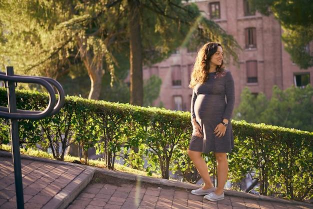 Jonge zwangere vrouw waring grijze jurk staat gelukkig in het park onder het zonlicht