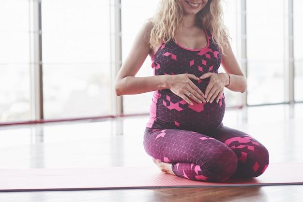 Jonge zwangere vrouw zit in de hal en houdt de handen op haar buik om de vorm van het hart te creëren.