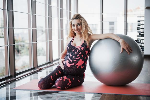 Jonge zwangere vrouw zitten en met een kogel voor oefeningen.