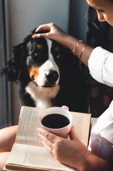 Jonge zwangere vrouw zitten in de woonkamer met haar schattige hond, lezen en koffie drinken