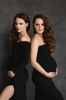 Jonge zwangere vrouwen in zwarte jurken met grote buikjes.