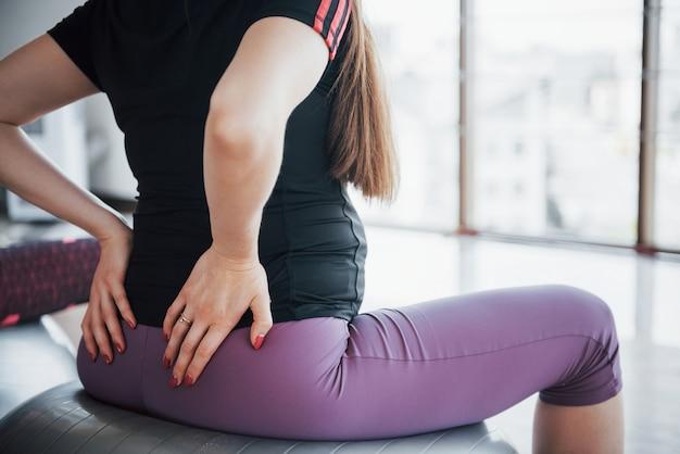 Jonge zwangere vrouwen zitten op de bal voor oefeningen in de sportschool