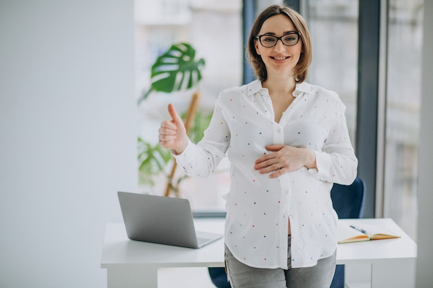 Jonge zwangere zakenvrouw permanent op kantoor