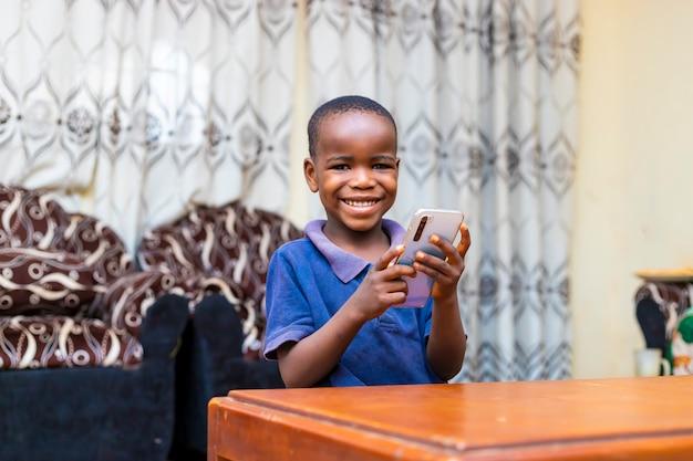 Jonge zwarte afrikaanse jongen zittend aan een tafel thuis met behulp van zijn mobiele telefoon voor online leren tijdens de vergrendelingsperiode.