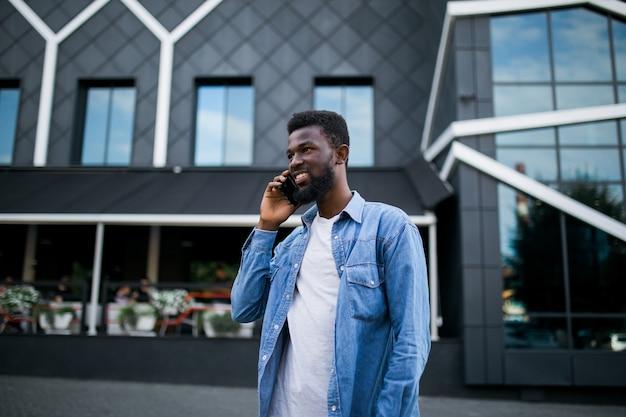 Jonge zwarte afrikaanse man glimlachend en praten op mobiele telefoon buiten