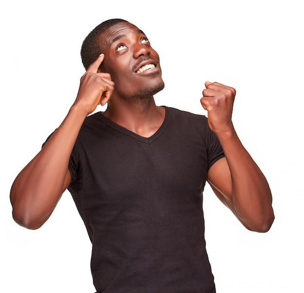 Jonge zwarte afrikaanse mens die en over iets denkt ophaalt