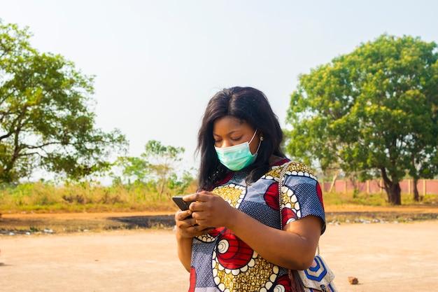 Jonge zwarte afrikaanse vrouwelijke bedrijfsvrouw die gezichtsmasker draagt dat internet controleert.