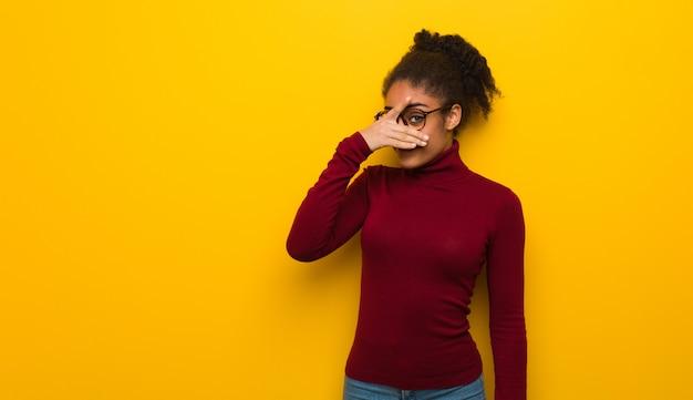 Jonge zwarte afro-amerikaanse meid met blauwe ogen beschaamd en lachen op hetzelfde moment