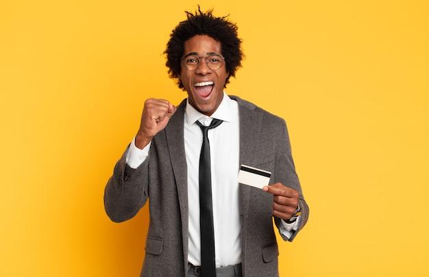 Jonge zwarte afro man agressief schreeuwen met een boze uitdrukking of met gebalde vuisten het vieren van succes