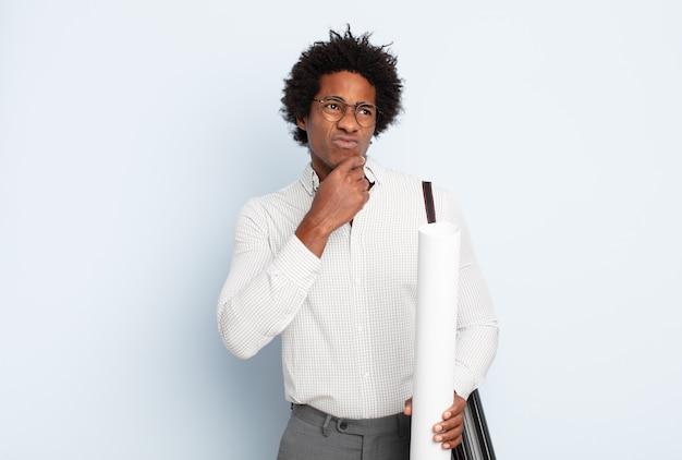 Jonge zwarte afro man denken, twijfelachtig en verward voelen, met verschillende opties, zich afvragend welke beslissing te nemen