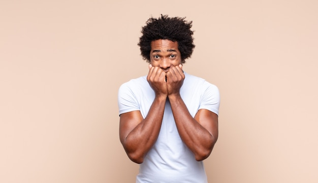 Jonge zwarte afro man die bezorgd, gestrest, angstig en bang kijkt, in paniek raakt en tanden op elkaar klemt