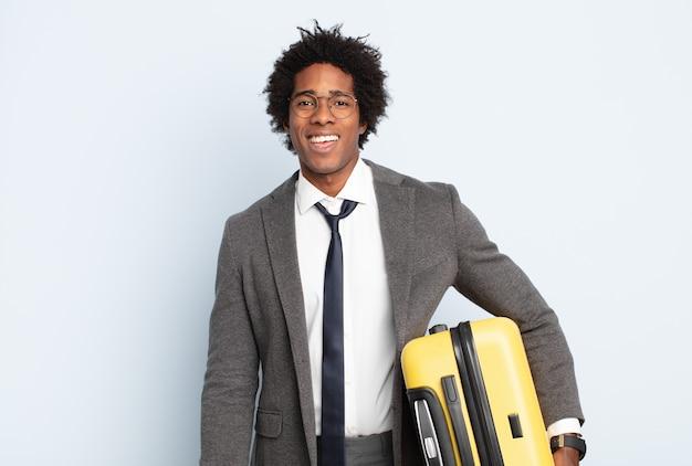 Jonge zwarte afro man die blij en aangenaam verrast kijkt, opgewonden met een gefascineerde en geschokte uitdrukking