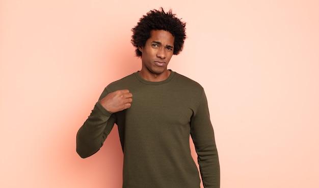 Jonge zwarte afro-man die er arrogant, succesvol, positief en trots uitziet, wijzend naar zichzelf