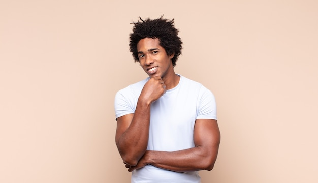 Jonge zwarte afro-man die er extreem blij en verrast uitziet, succes viert, schreeuwt en springt