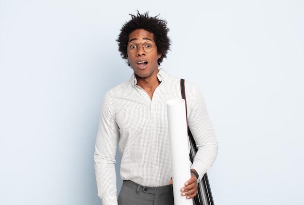 Jonge zwarte afro-man die erg geschokt of verrast kijkt, starend met open mond en zegt wow