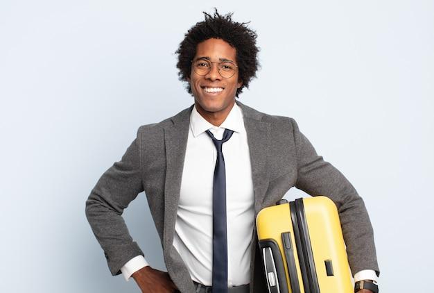 Jonge zwarte afro-man die gelukkig lacht met een hand op de heup en een zelfverzekerde, positieve, trotse en vriendelijke houding
