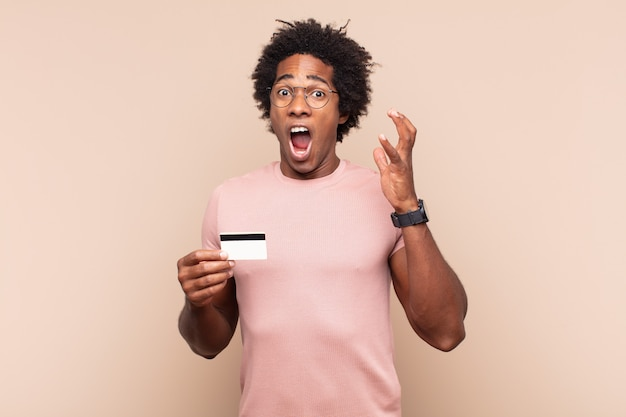 Jonge zwarte afro-man die met zijn handen in de lucht schreeuwt, zich woedend, gefrustreerd, gestrest en overstuur voelt
