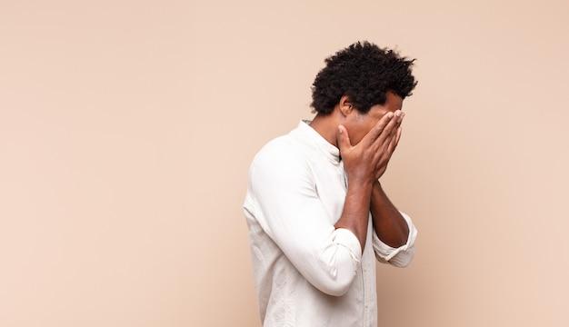Jonge zwarte afro man die ogen bedekt met handen met een droevige, gefrustreerde blik van wanhoop, huilen, zijaanzicht
