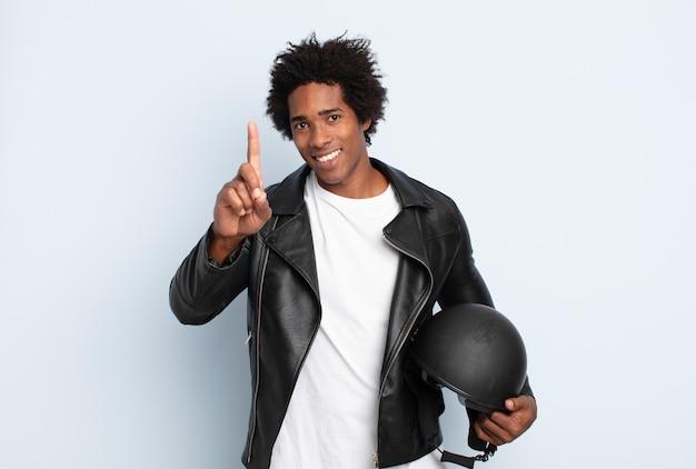 Jonge zwarte afro-man die trots en zelfverzekerd glimlacht en nummer één triomfantelijk poseert en zich een leider voelt