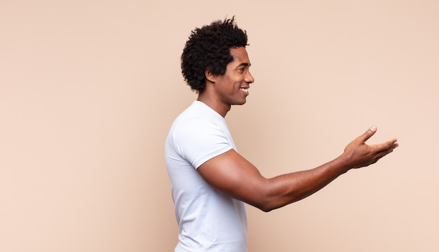 Jonge zwarte afro man die trots en zelfverzekerd glimlacht, zich gelukkig en tevreden voelt en een concept op kopie ruimte toont