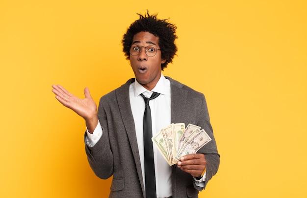Jonge zwarte afro man die verbaasd en geschokt kijkt, met open mond een voorwerp met een open hand aan de zijkant