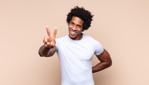 Jonge zwarte afro man die verdrietig, teleurgesteld of boos kijkt, duimen naar beneden laat zien in onenigheid, zich gefrustreerd voelt