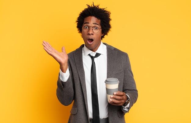 Jonge zwarte afro-man die verrast en geschokt kijkt, met open mond terwijl hij een object vasthoudt met een open hand aan de zijkant
