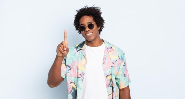 Jonge zwarte afro man die vriendelijk glimlacht en kijkt, nummer één toont of eerst met de hand naar voren, aftellend