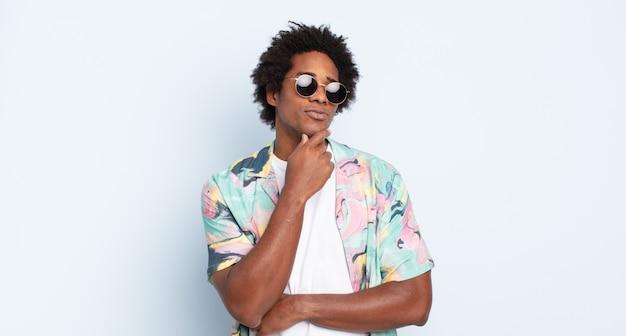 Jonge zwarte afro-man die vrolijk lacht en dagdroomt of twijfelt, opzij kijkend