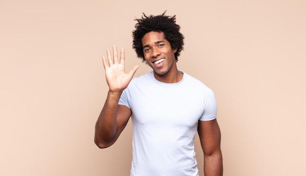 Jonge zwarte afro-man die vrolijk lacht en naar de camera wijst terwijl hij je later een gebaar maakt, pratend aan de telefoon
