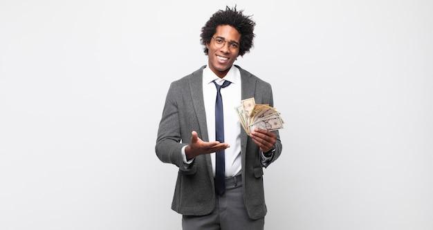 Jonge zwarte afro man die vrolijk lacht, zich gelukkig voelt en een concept toont in kopie ruimte met handpalm