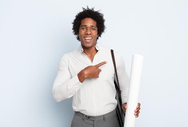 Jonge zwarte afro man die vrolijk lacht, zich gelukkig voelt en naar de zijkant en naar boven wijst, object in kopie ruimte toont