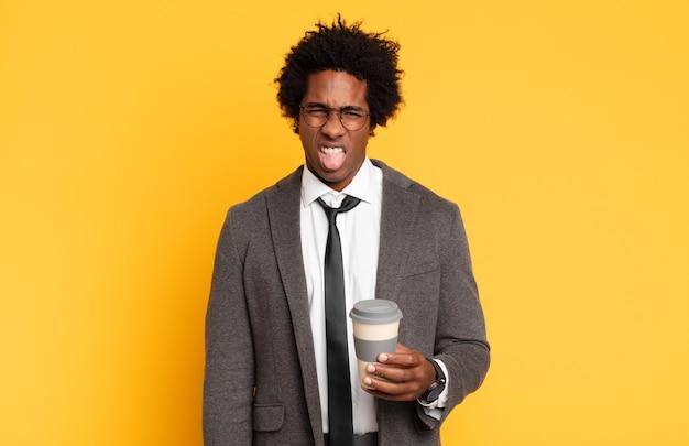 Jonge zwarte afro man die walgt en geïrriteerd voelt, tong uitsteekt, niet van iets smerigs en vies houdt
