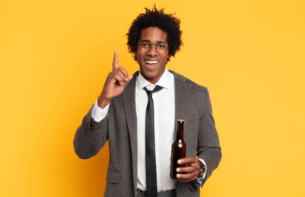 Jonge zwarte afro-man die zich als een gelukkig en opgewonden genie voelt na het realiseren van een idee, opgewekt de vinger opstekend, eureka!