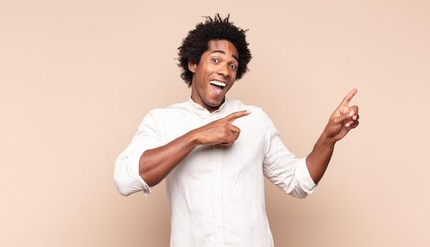 Jonge zwarte afro-man die zich blij en verrast voelt, lacht met een geschokte uitdrukking en naar de zijkant wijst