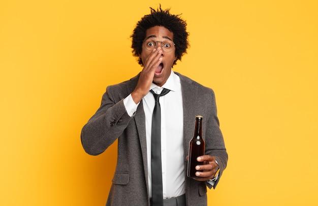 Jonge zwarte afro man die zich blij, opgewonden en positief voelt, een grote schreeuw geeft met de handen naast de mond, roept