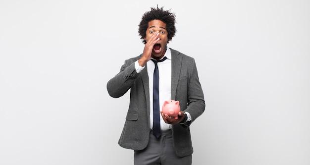 Jonge zwarte afro man die zich blij, opgewonden en positief voelt, een grote schreeuw geeft met handen naast de mond, roept