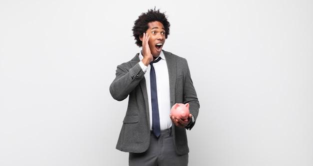 Jonge zwarte afro man die zich blij, opgewonden en verrast voelt, naar de zijkant kijkend met beide handen op het gezicht
