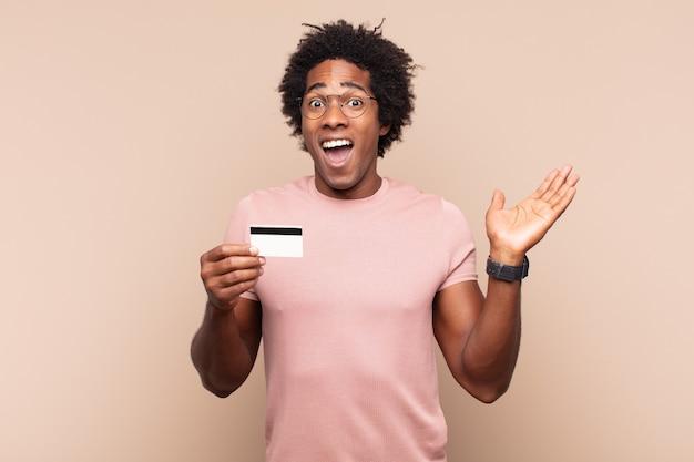 Jonge zwarte afro man die zich blij, opgewonden, verrast of geschokt voelt, glimlachend en verbaasd over iets ongelooflijks