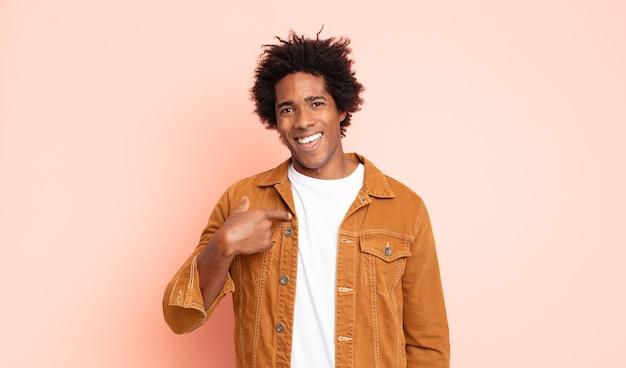 Jonge zwarte afro man die zich blij, verrast en trots voelt, naar zichzelf wijzend met een opgewonden, verbaasde blik