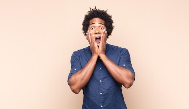 Jonge zwarte afro man die zich blij, verrast en trots voelt, schreeuwt en succes viert met een grote glimlach