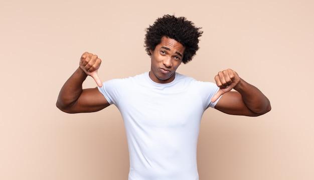 Jonge zwarte afro man die zich boos, boos, geïrriteerd, teleurgesteld of ontevreden voelt, duimen naar beneden toont met een serieuze blik