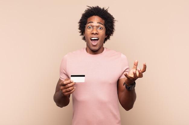 Jonge zwarte afro man die zich extreem geschokt en verrast, angstig en in paniek voelt, met een gestreste en geschokte blik