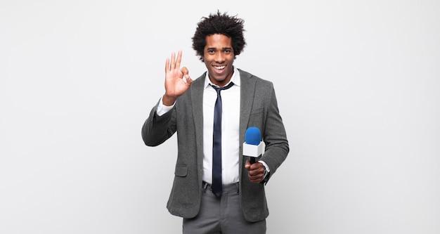 Jonge zwarte afro-man die zich gelukkig, ontspannen en tevreden voelt, goedkeuring toont met een goed gebaar