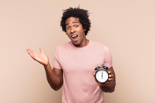 Jonge zwarte afro-man die zich gelukkig, opgewonden, verrast of geschokt voelt, glimlacht en verbaasd over iets ongelooflijks