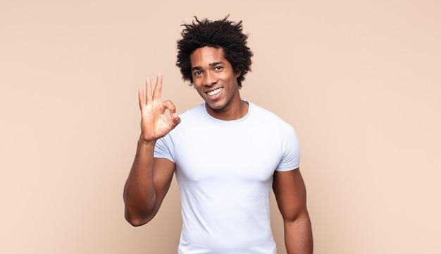 Jonge zwarte afro-man die zich gelukkig, verbaasd, tevreden en verrast voelt, oke toont en duimen omhoog gebaren, glimlachend