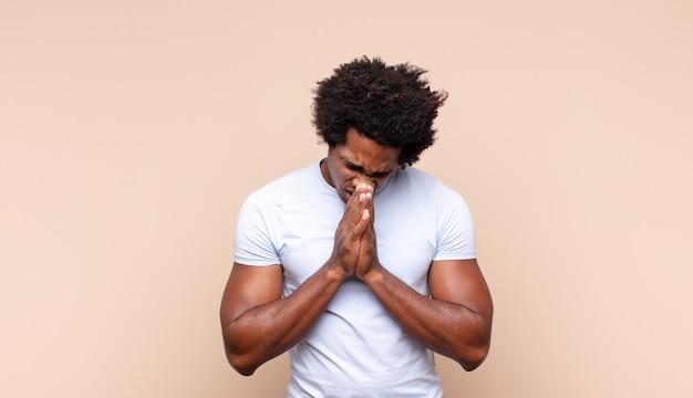 Jonge zwarte afro man die zich gelukkig, vriendelijk en positief voelt, lacht en een portret of fotolijst met handen maakt