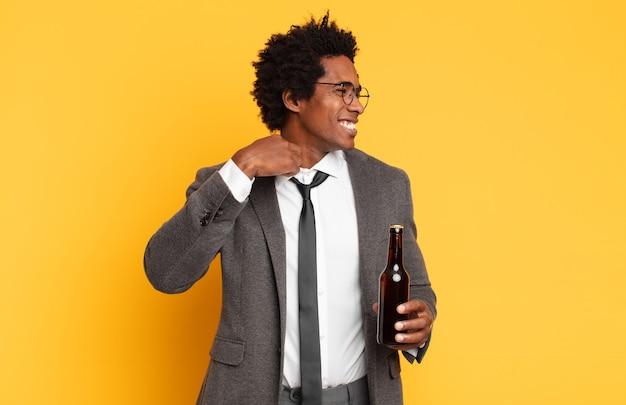 Jonge zwarte afro man die zich gestrest, angstig, moe en gefrustreerd voelt, de nek van het shirt trekt, gefrustreerd kijkt door het probleem
