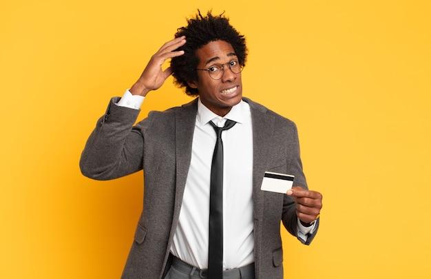 Jonge zwarte afro-man die zich gestrest, bezorgd, angstig of bang voelt, met de handen op het hoofd, in paniek bij vergissing